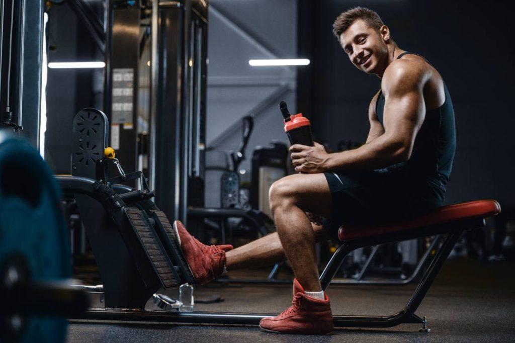 muž v posilke pije bcaa aminokyseliny