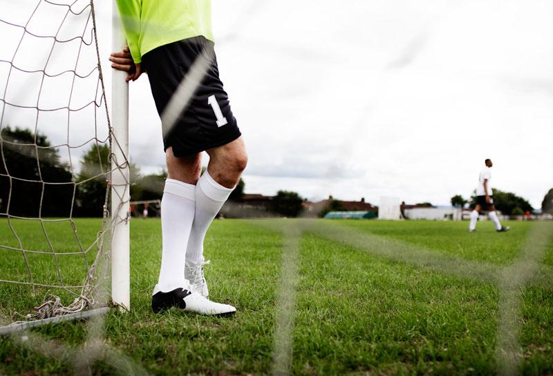 brankár opierajúci sa o futbalovú bránku