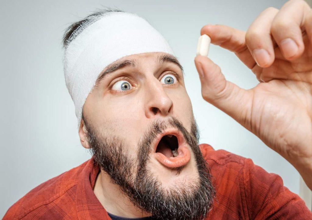 muž pozerá na bielu tabletku