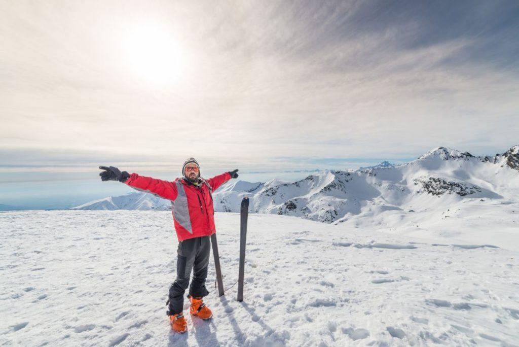 muž na svahu v červenej lyžiarskej bunde