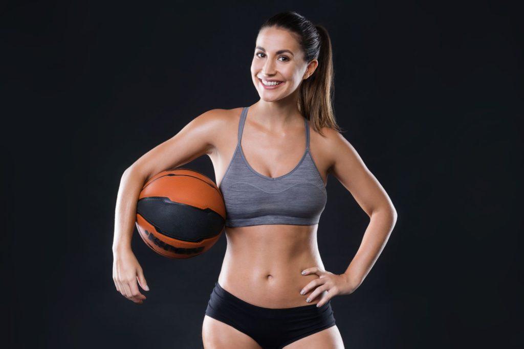 sivá športová podprsenka a žena s loptou