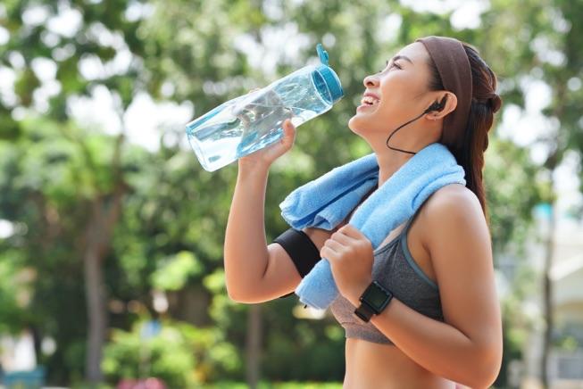 žena s fľašou vody v ruke
