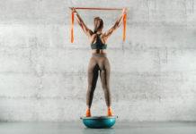 žena cvičiaca s expanderom na bosu lopte