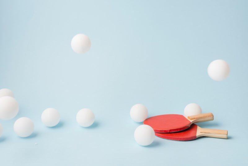 biele loptičky a dve pingpongové rakety